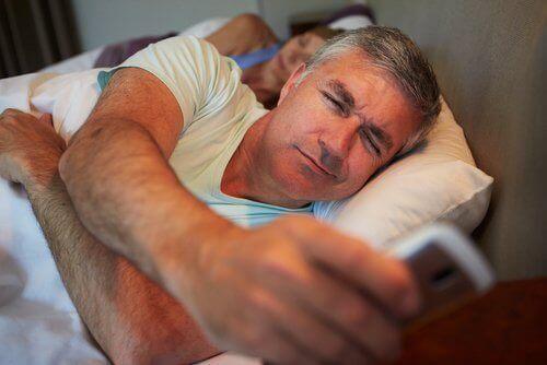 mies vilkaisee puhelintaan sängyssä