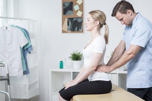 nainen lääkärin vastaanotolla selkäkivun takia