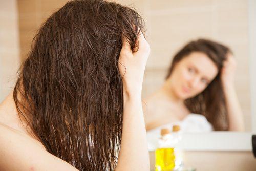 nainen kosteuttaa kuivaa tukkaa