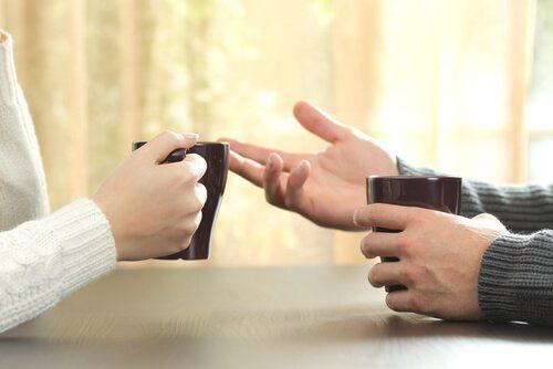 kaksi ihmistä kahvilla käyttävät kehonkieltä