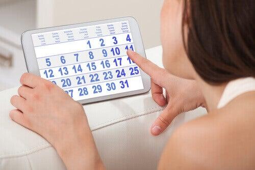 nainen katsoo kalenteria