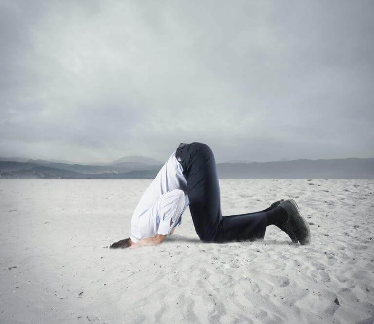mies työnsi päänsä hiekkaan