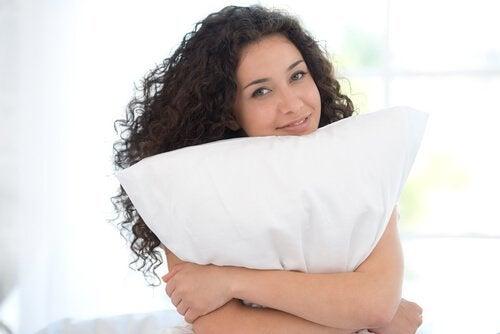 nainen halaa tyynyään
