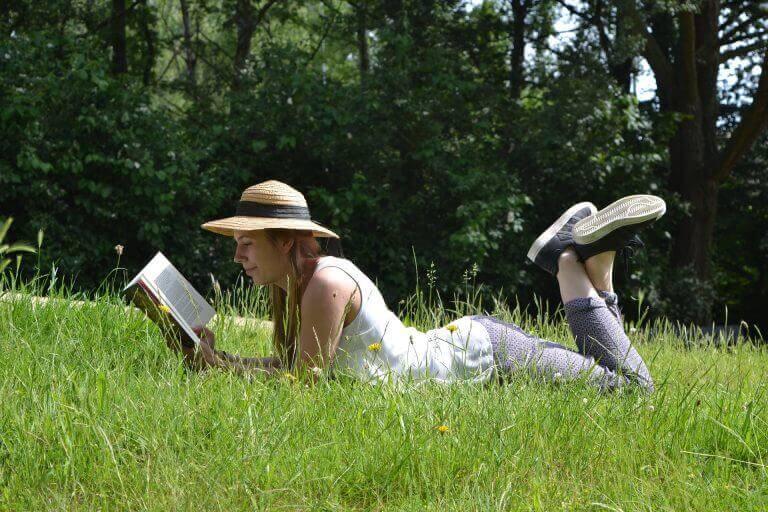 nainen lukee nurmikolla