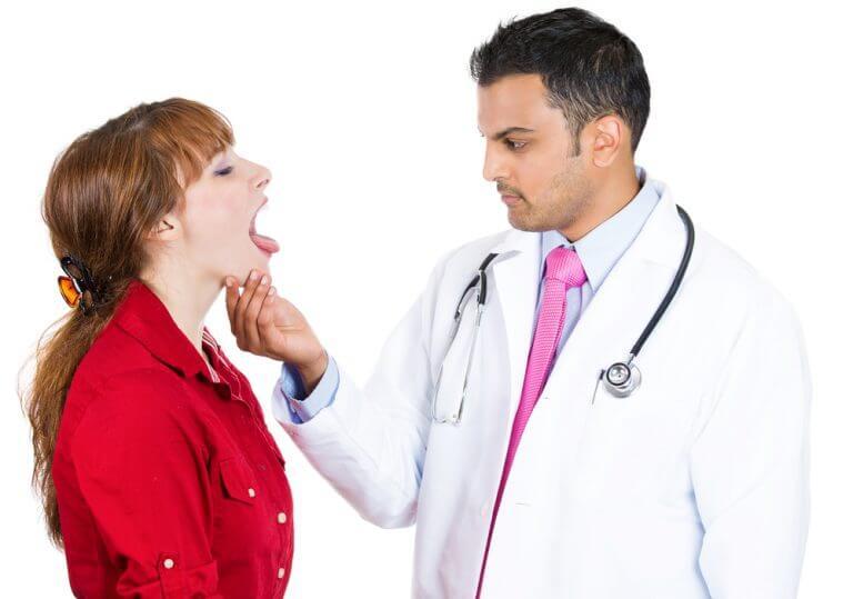 lääkäri tutkii naisen suun