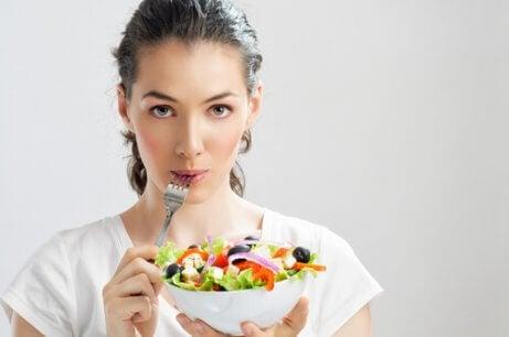 nainen syö salaattia välttääkseen epigastralgia