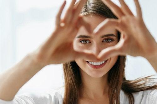 muodostaa sydämen käsillään