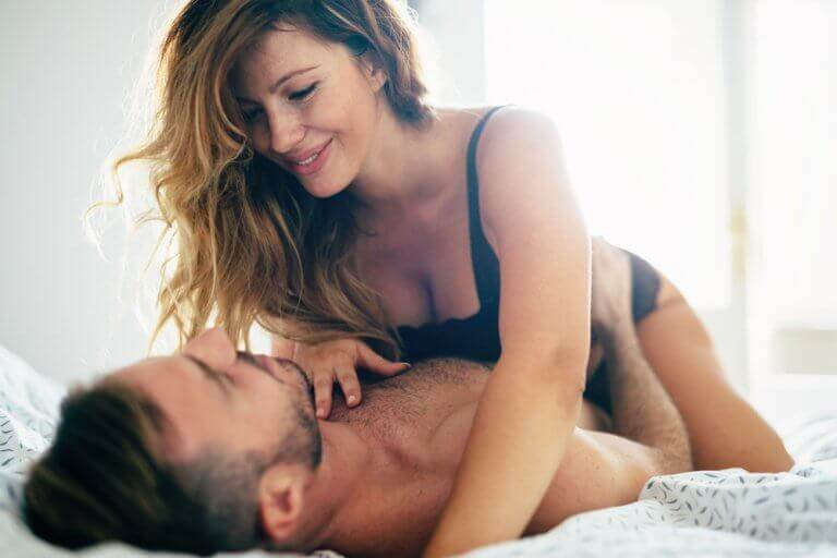 nainen ja mies leikittelevät sängyssä