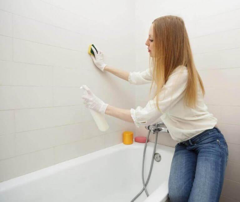 nainen puhdistaa kylppärin seiniä