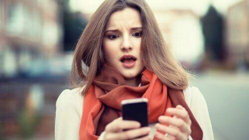nainen katsoo puhelintaan