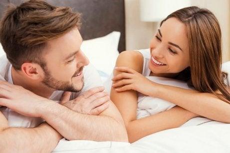 nainen ja mies juttelevat sängyssä