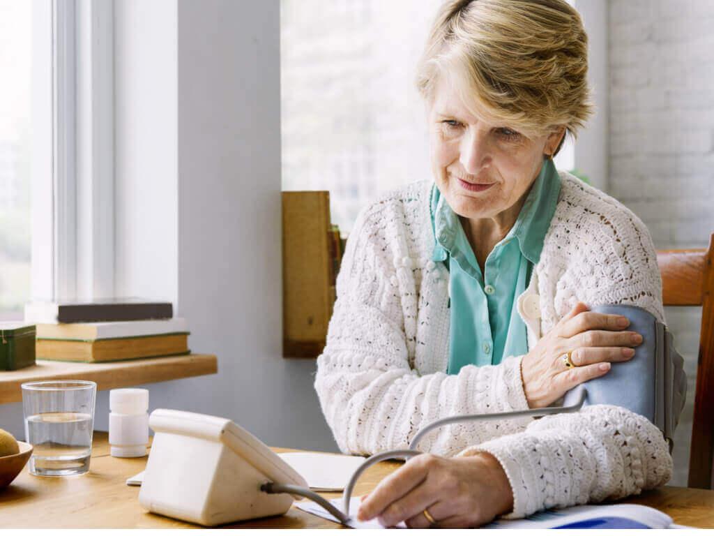 nainen mittaa verenpaineensa kotona