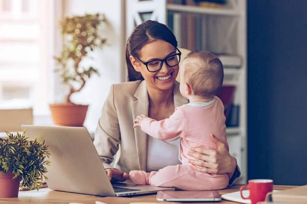 äiti tekee töitä ja vauva istuu pöydällä