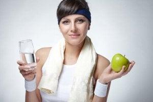 nainen harrastaa liikunta ja juo lasin vettä ja syö omenan