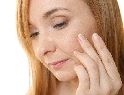 nainen tarkastelee ihoaan