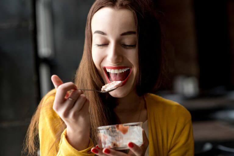 nainen syö herkullista jälkiruokaa