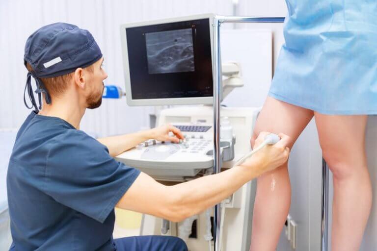 lääkäri tutkii jalkoja