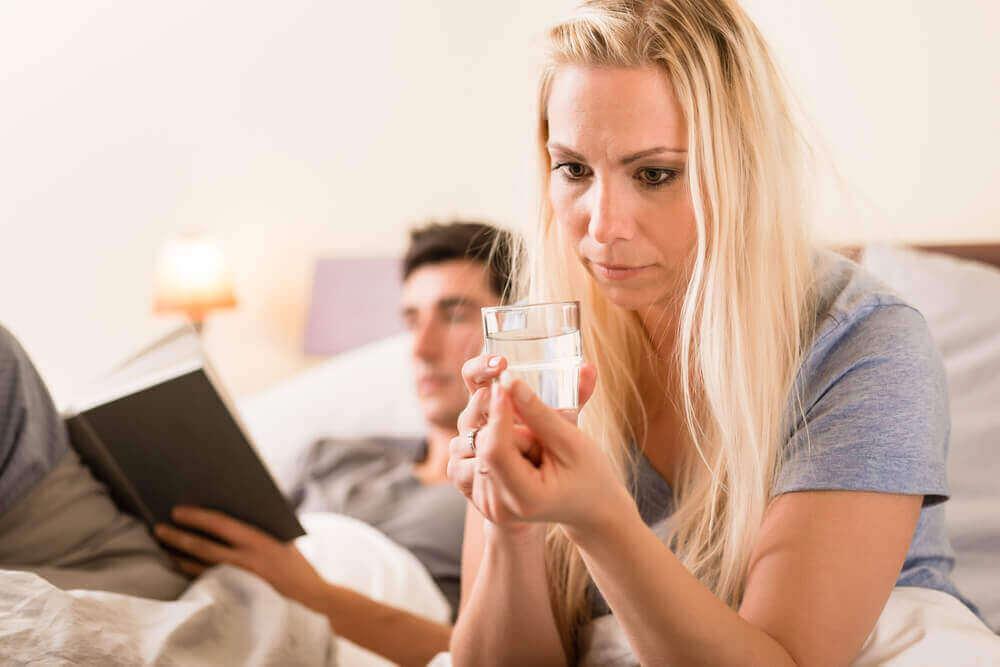 nainen ottaa pillerin