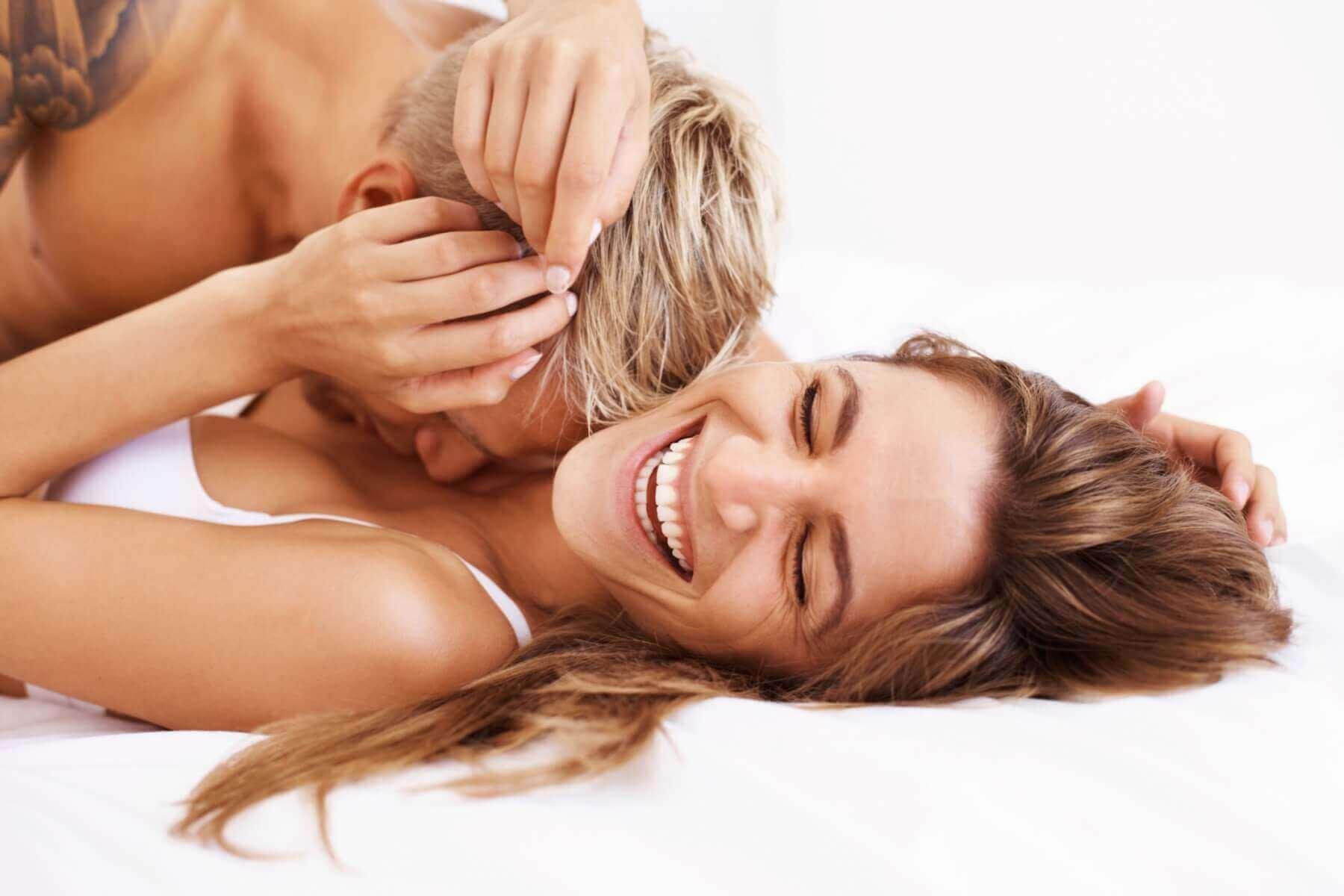 naurava nainen sängyssä miehen kanssa
