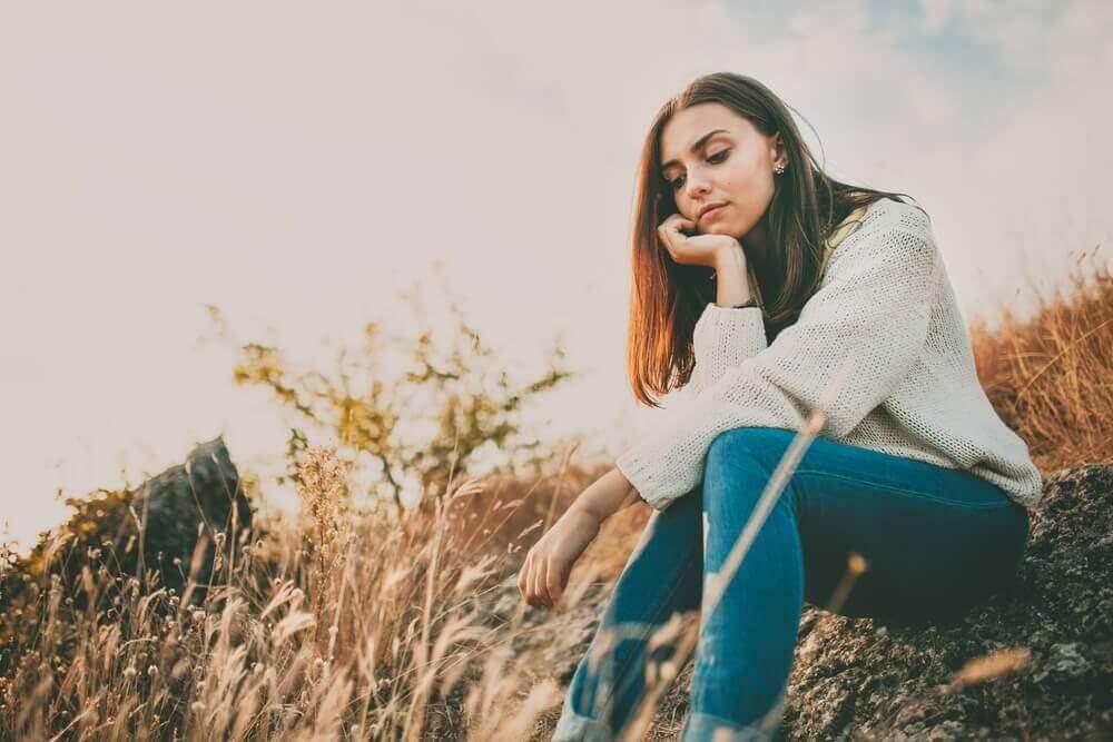 nainen istuskelee ulkona mietteissään