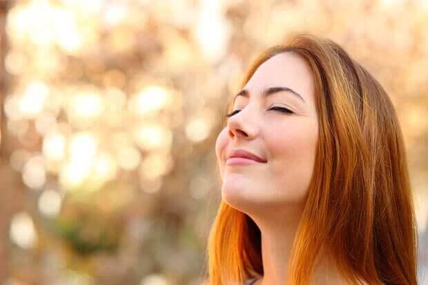 nainen hymyilee silmät kiinni