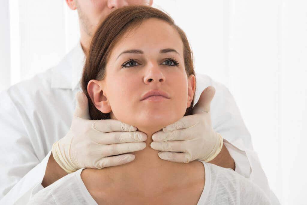 lääkäri tunnustelee naisen kaulaa