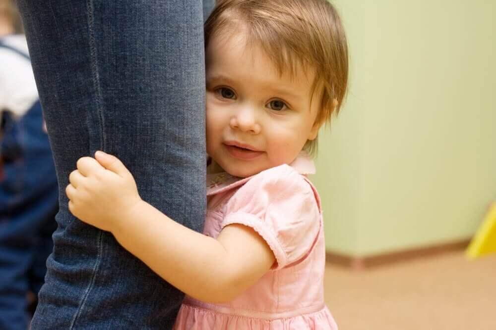 pieni tyttö äidin jalassa kiinni
