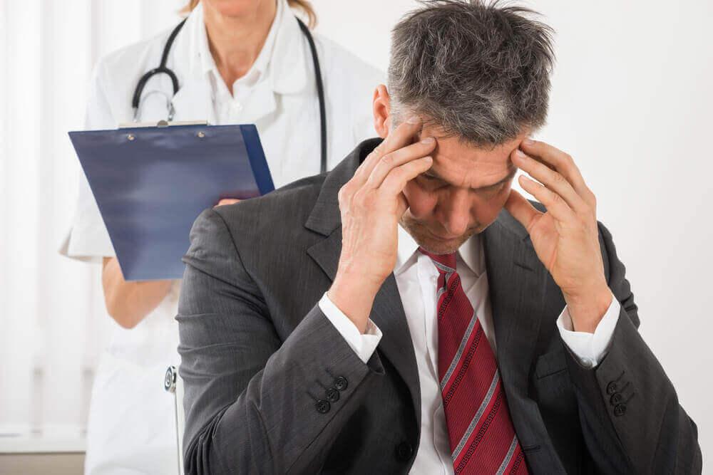 mies hakee lääkäriltä apua päänsärkyyn