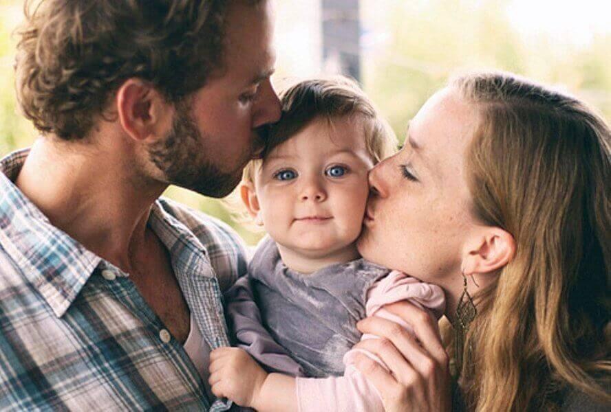 vanhemmat suukottavat tyttöä