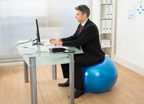 mies tekee töitä pilatespallon päällä