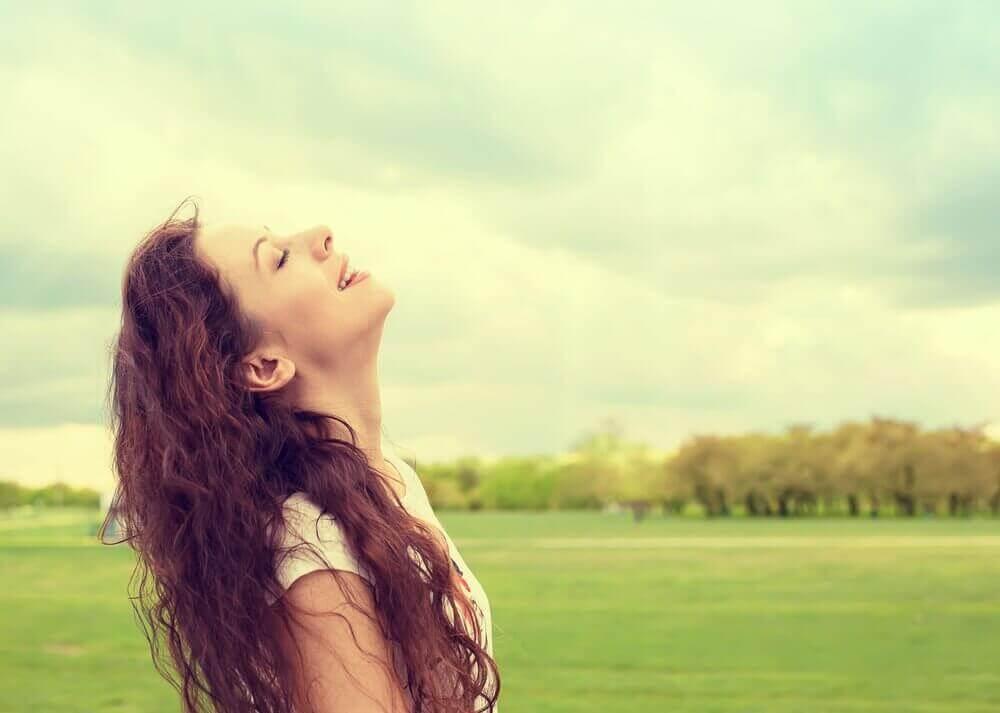 nainen hengittää raikasta ilmaa