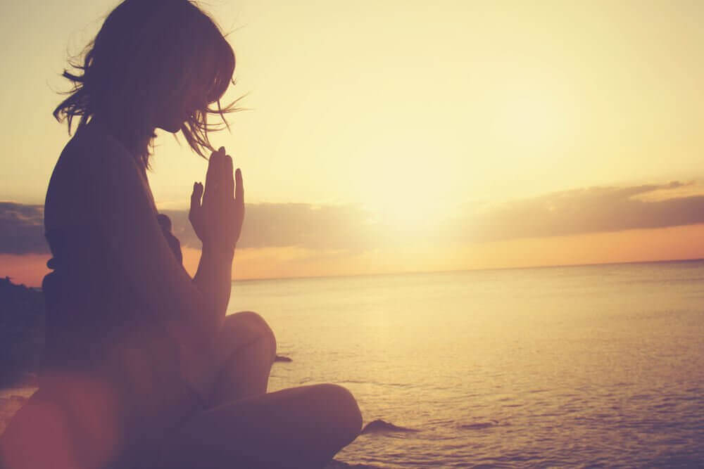 nainen meditoi rannalla