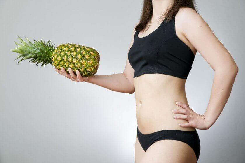 nainen seisoo ananas kädessä