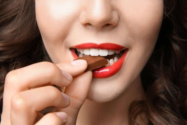 nainen syö palan suklaata