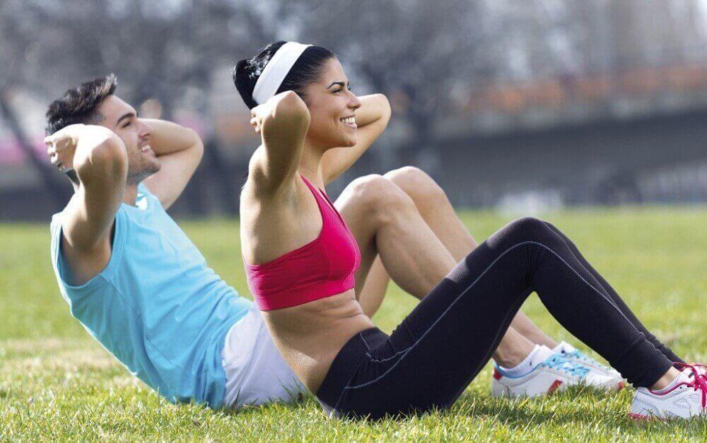 mies ja nainen tekevät vatsalihasliikkeitä