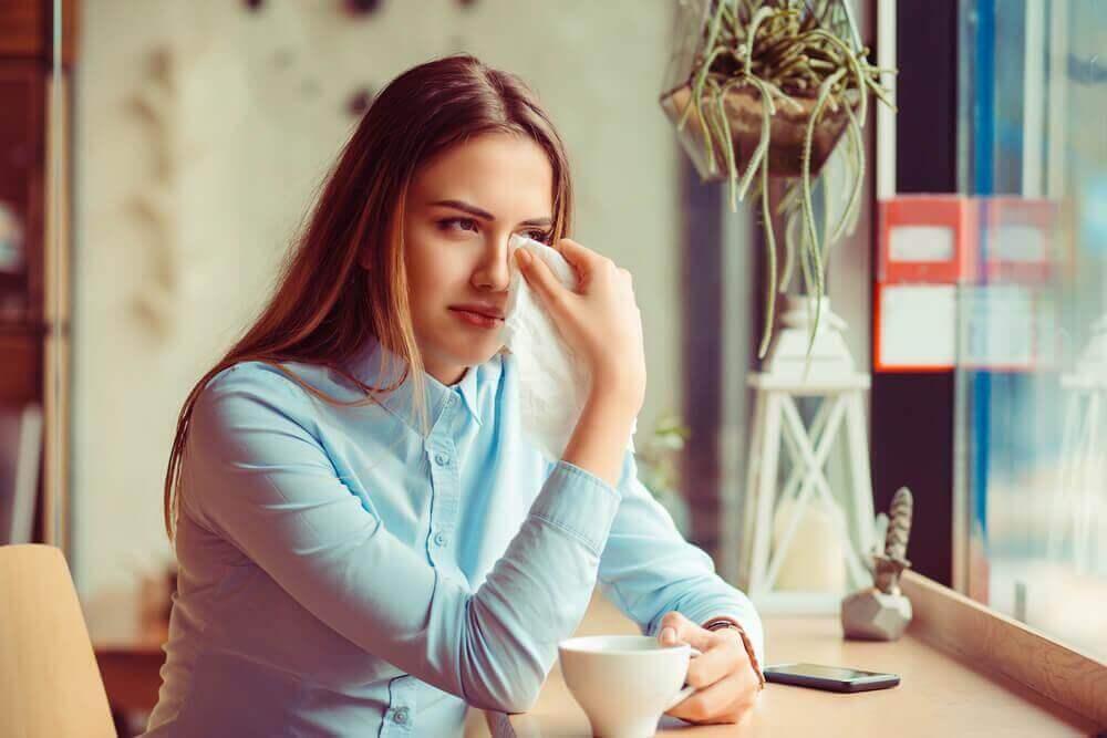 nuori nainen pyyhkii kyyneliä kasvoiltaan