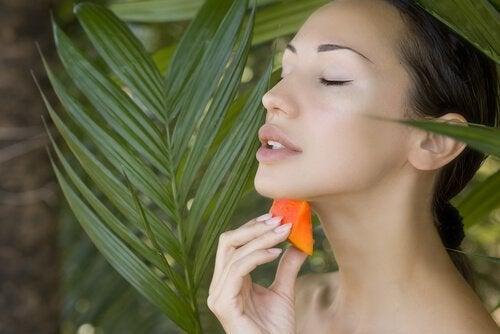 nainen laittaa papaijaa iholleen