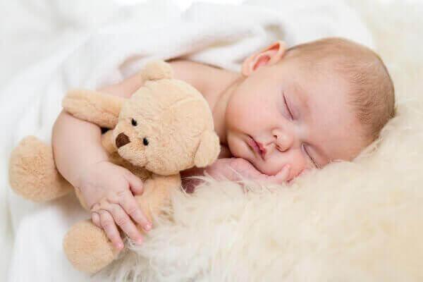 pieni vauva nukkuu nalle kainalossaan