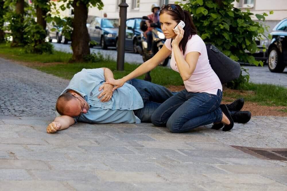 nainen soittaa ambulanssin miehelle joka makaa maassa