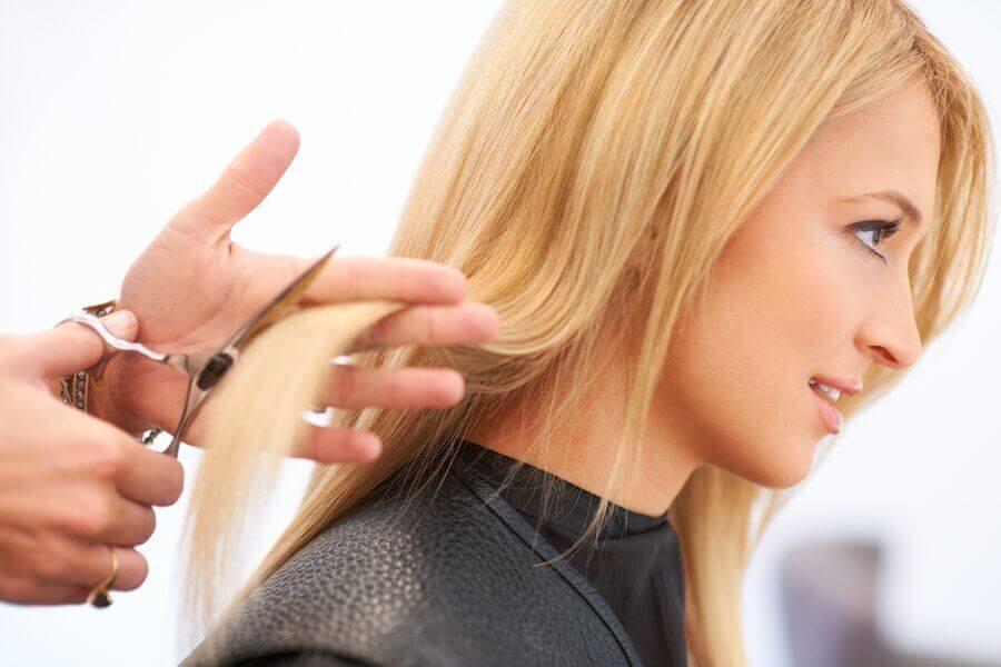 nainen leikkauttaa hiuksensa