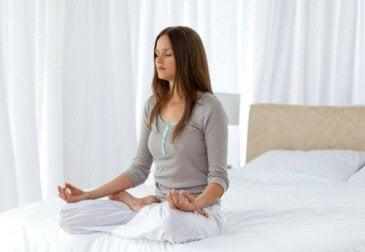 nainen meditoi sängyssä