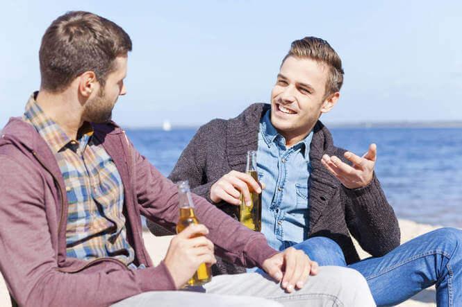 miehet oluella merenrannalla