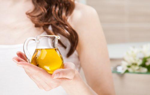nainen pitelee öljypulloa kädessään