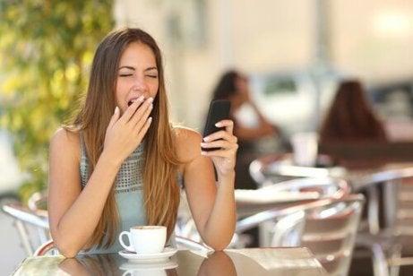 nainen juo kahvia ja haukottelee