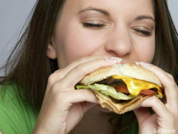 nainen syö hampurilaista