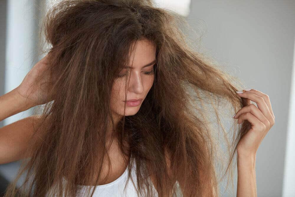 naisen hiukset ovat sotkuiset ja kähärät