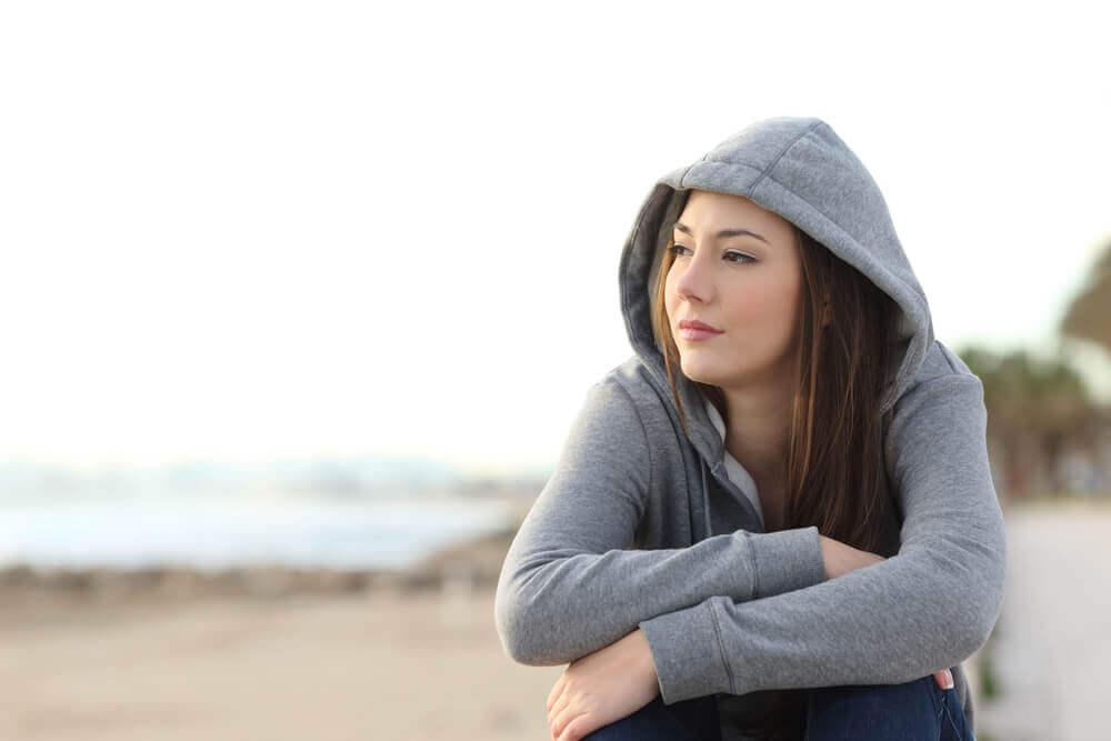 nuori istuu rannalla mietteliäänä