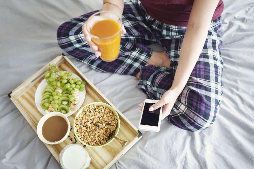 nainen syö aamupalaa sängyssä