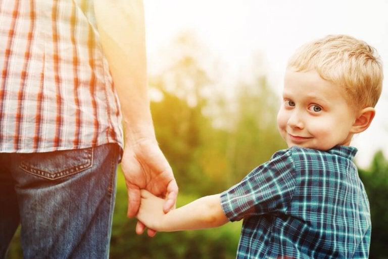 poika pitää isänsä kädestä kiinni