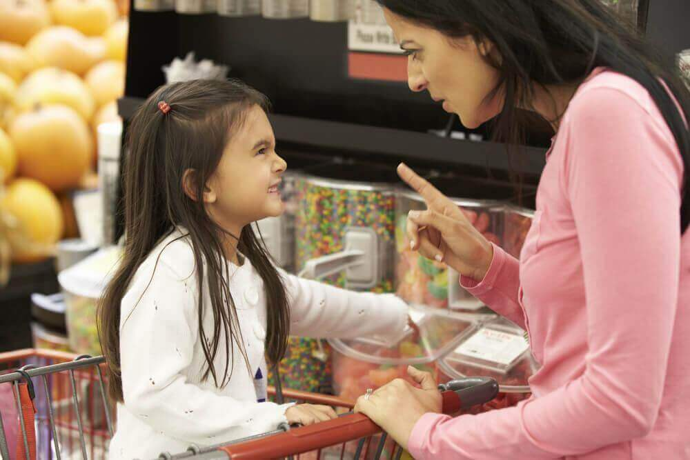 lapsi haluaa karkkia kaupassa